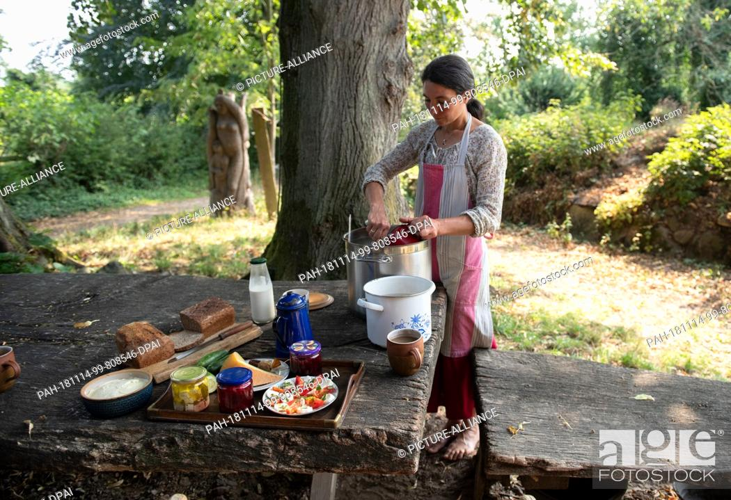 Stock Photo: 23 August 2018, Mecklenburg-Western Pomerania, Kalkhorst: Lina Schimmel is working on a cheese process in the garden in front of the main house.