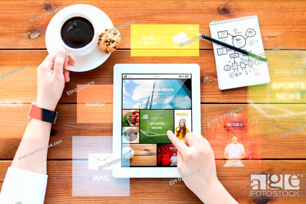 Stock Photo: business, technology, media and people concept - close up of woman with internet news on tablet pc computer screen, notebook and coffee on wooden table.