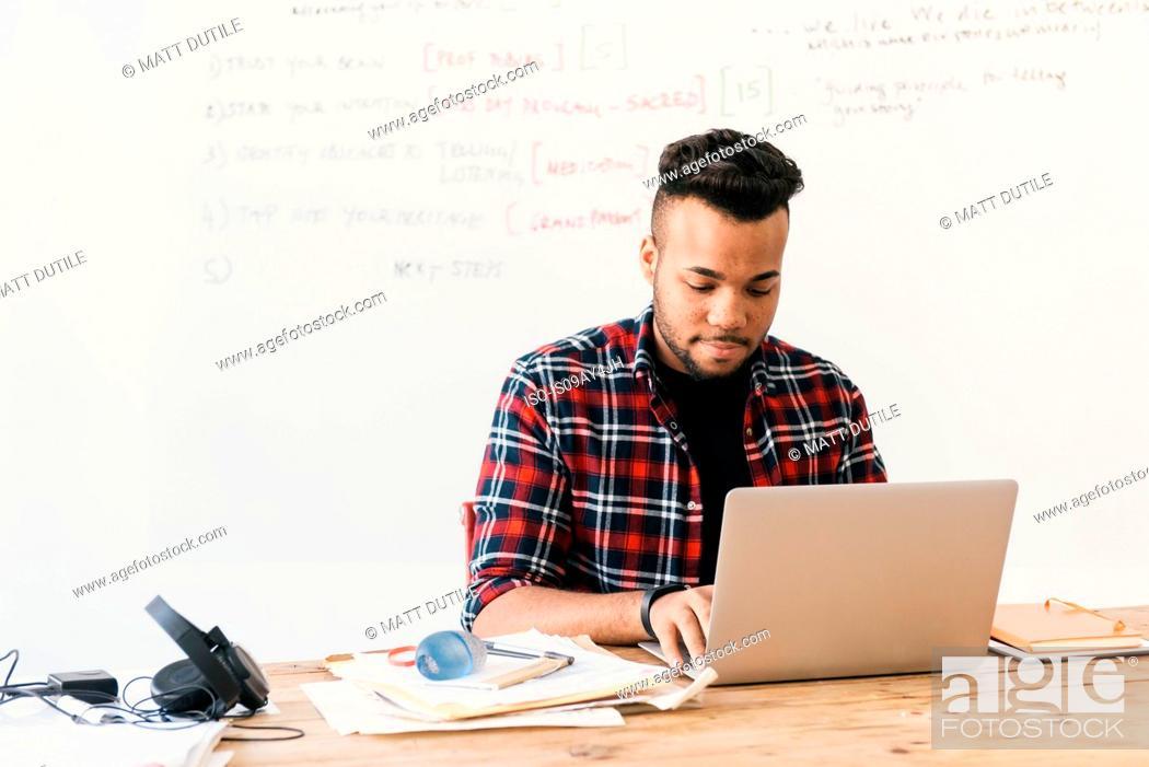 Stock Photo: Man at desk using laptop.