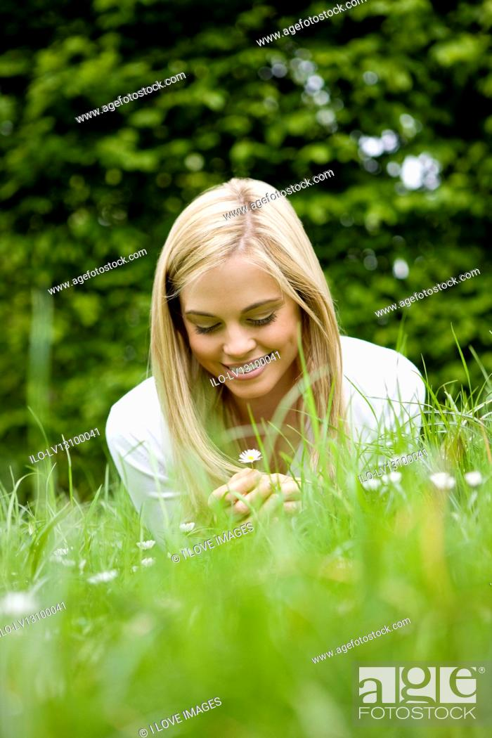 Stock Photo: A young woman lying on the grass, looking at a daisy.