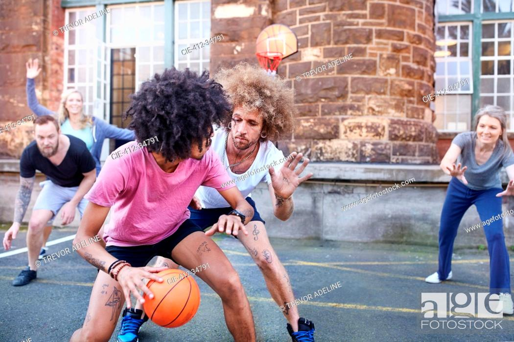 Stock Photo: Friends playing basketball on urban basketball court.