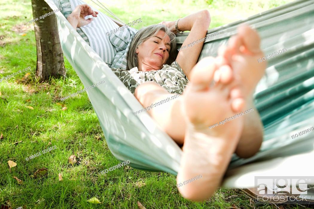 Stock Photo: Mature woman sleeping barefoot in hammock.