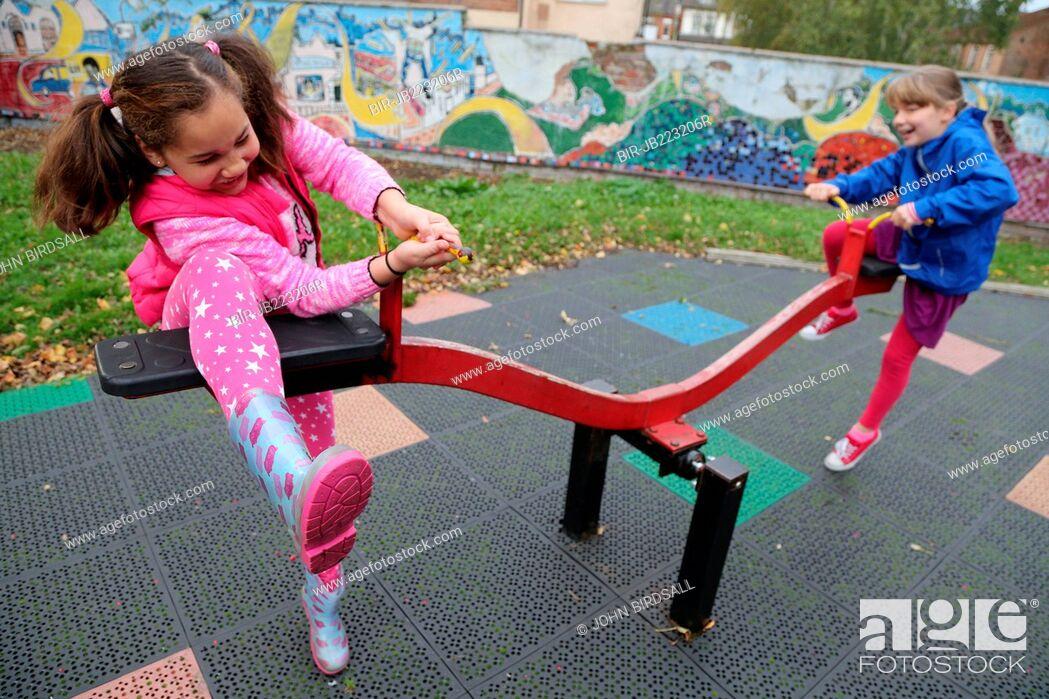 Imagen: Two girls on seesaw in urban park.