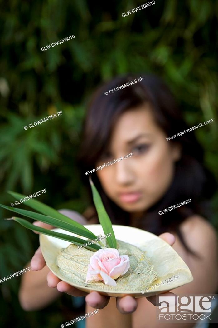 Stock Photo: Close-up of a young woman holding a bowl of herb.