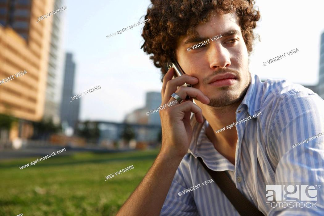 Stock Photo: Germany, Berlin, Young man using mobile phone, portrait.