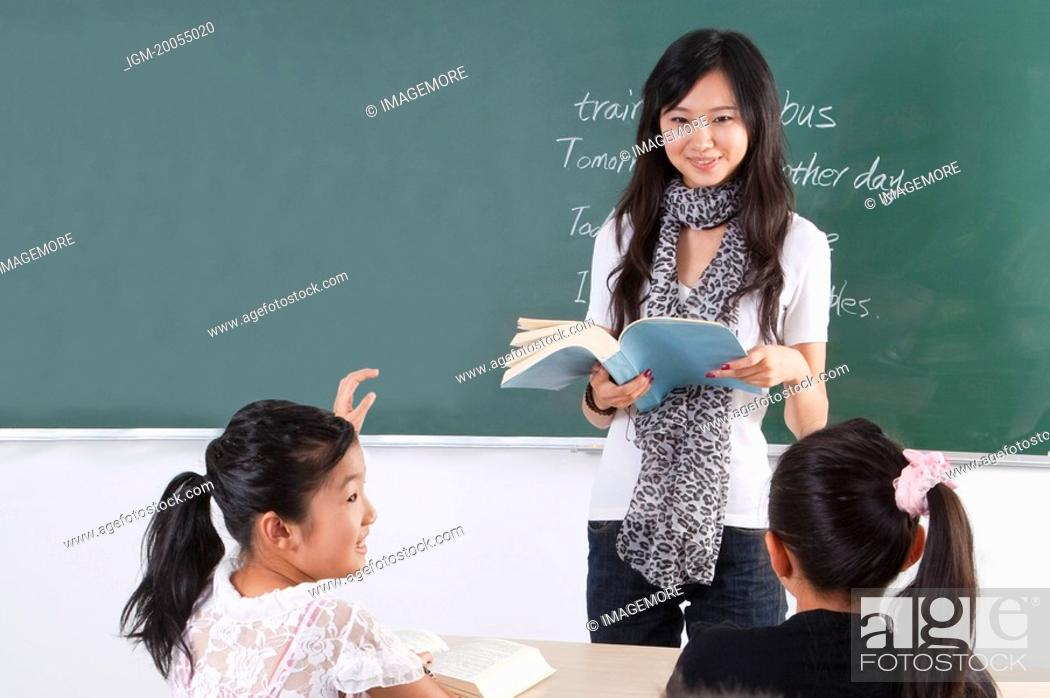 Stock Photo: Child, Young teacher teaching children and smiling in the classroom.