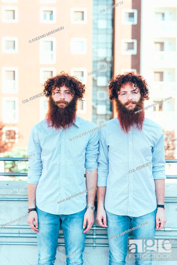 Imagen: Portrait of identical male hipster twins standing on apartment roof terrace.