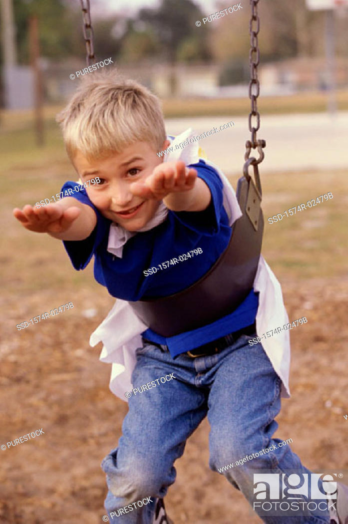 Stock Photo: Portrait of a boy hanging on a swing.