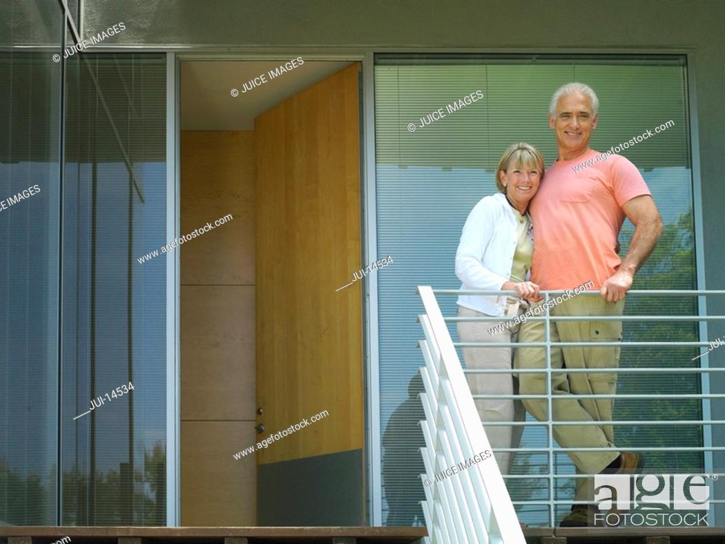 Stock Photo: Senior couple arm in arm on balcony, smiling, portrait, low angle view.