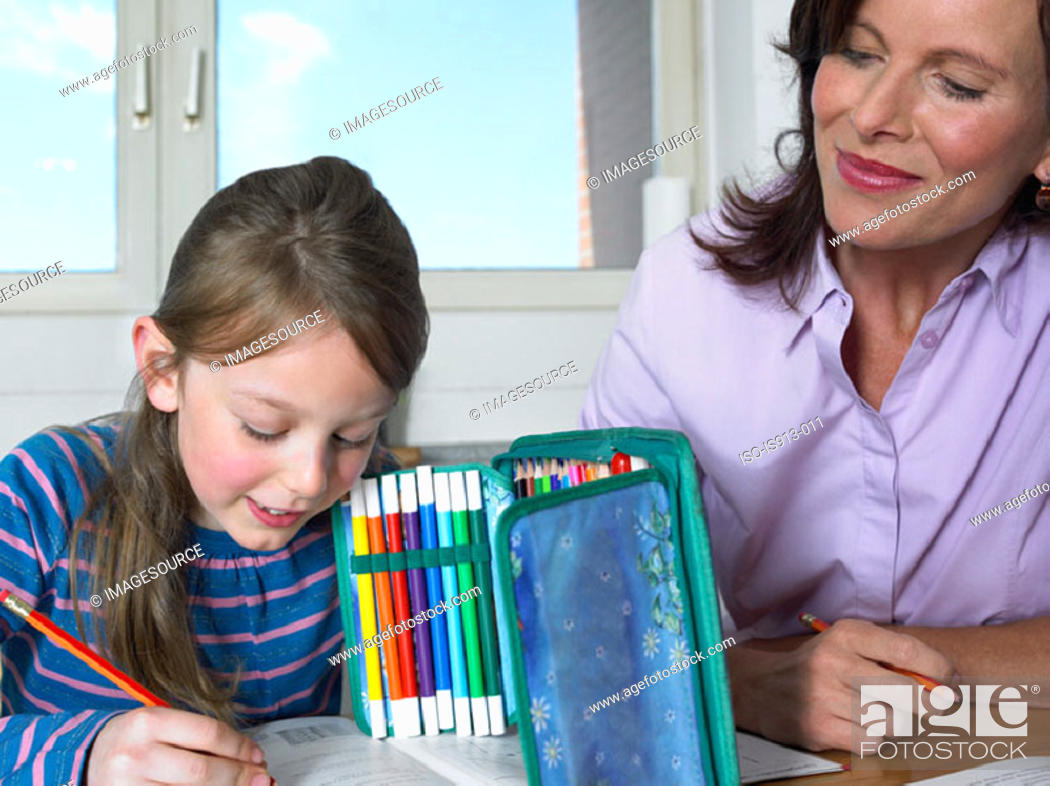Stock Photo: Mother watching daughter do homework.