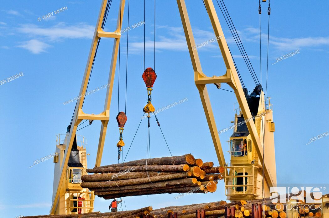Stock Photo: Ship mounted cranes lifting logs from dock onto log ship for transport to China; Port of Port Angeles, Washington USA.