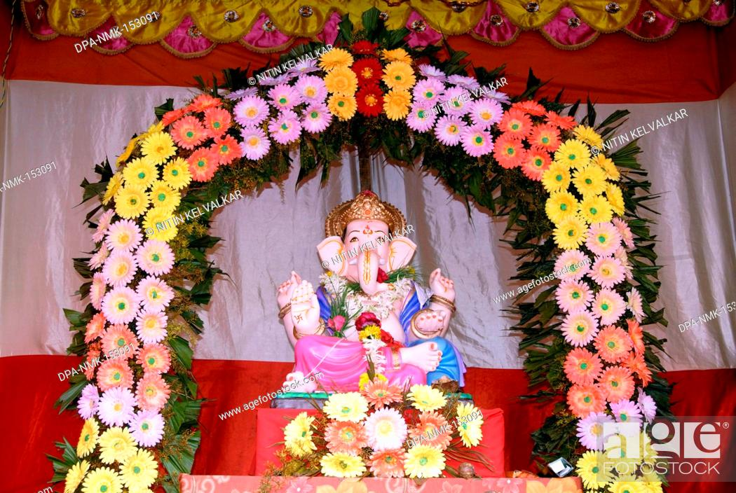 Idol of Lord Ganesh kept in gaily decorated frame of colourful ...