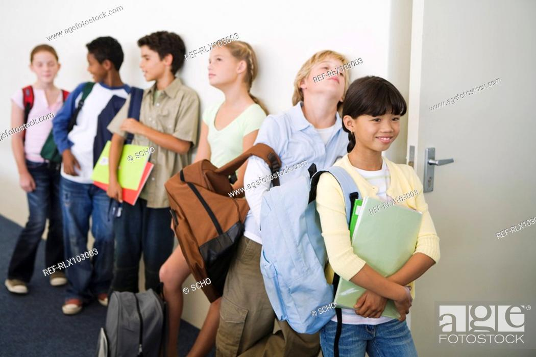 Stock Photo: Group of school children 10-13 waiting to enter classroom.
