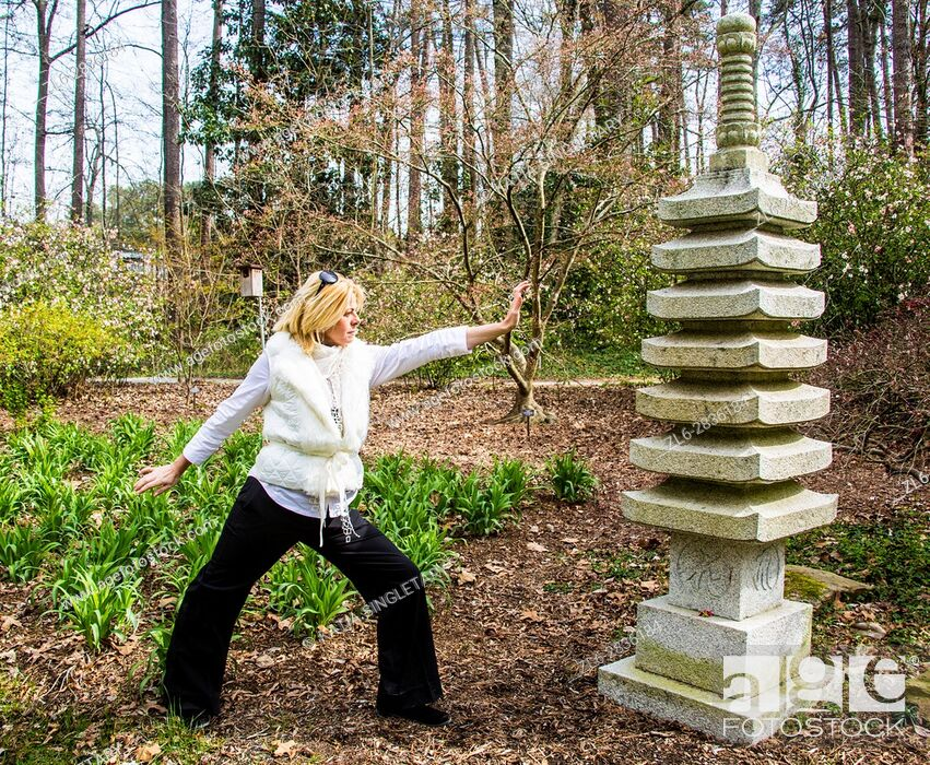 Stock Photo: Blond, caucasian woman wearing white taking yoga poses front of an Asian totem.