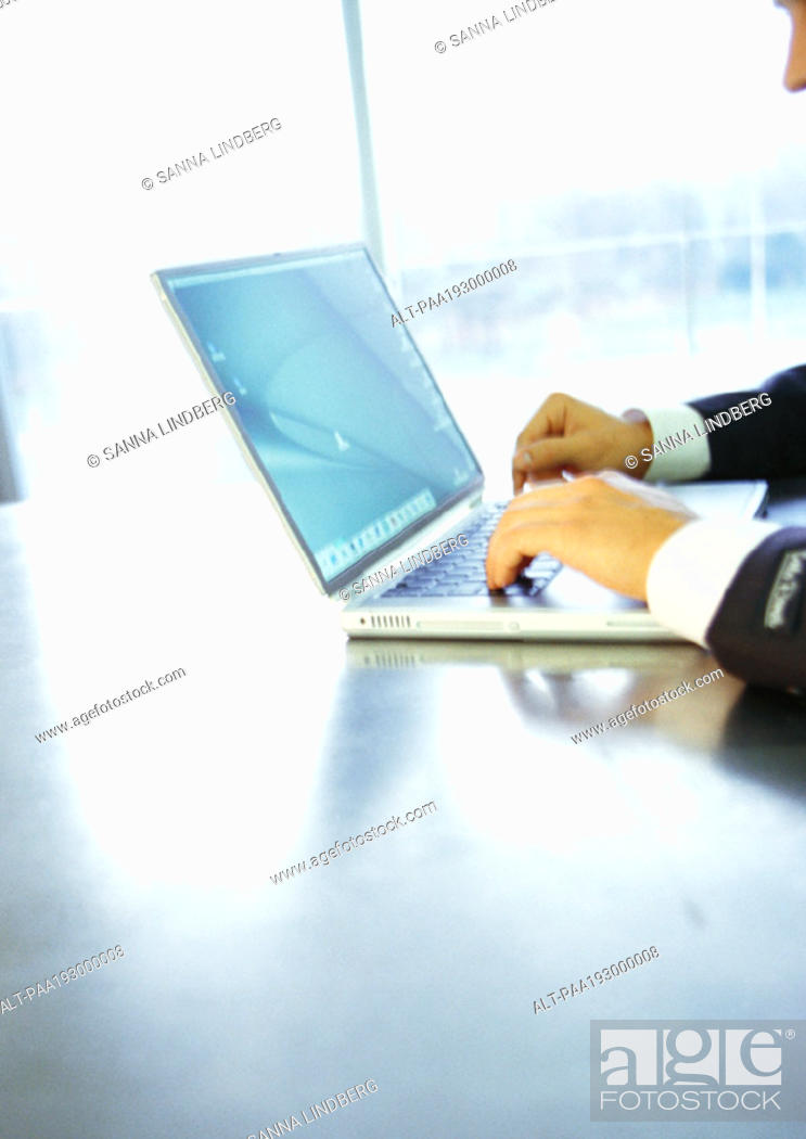Stock Photo: Man using laptop computer, partial view.