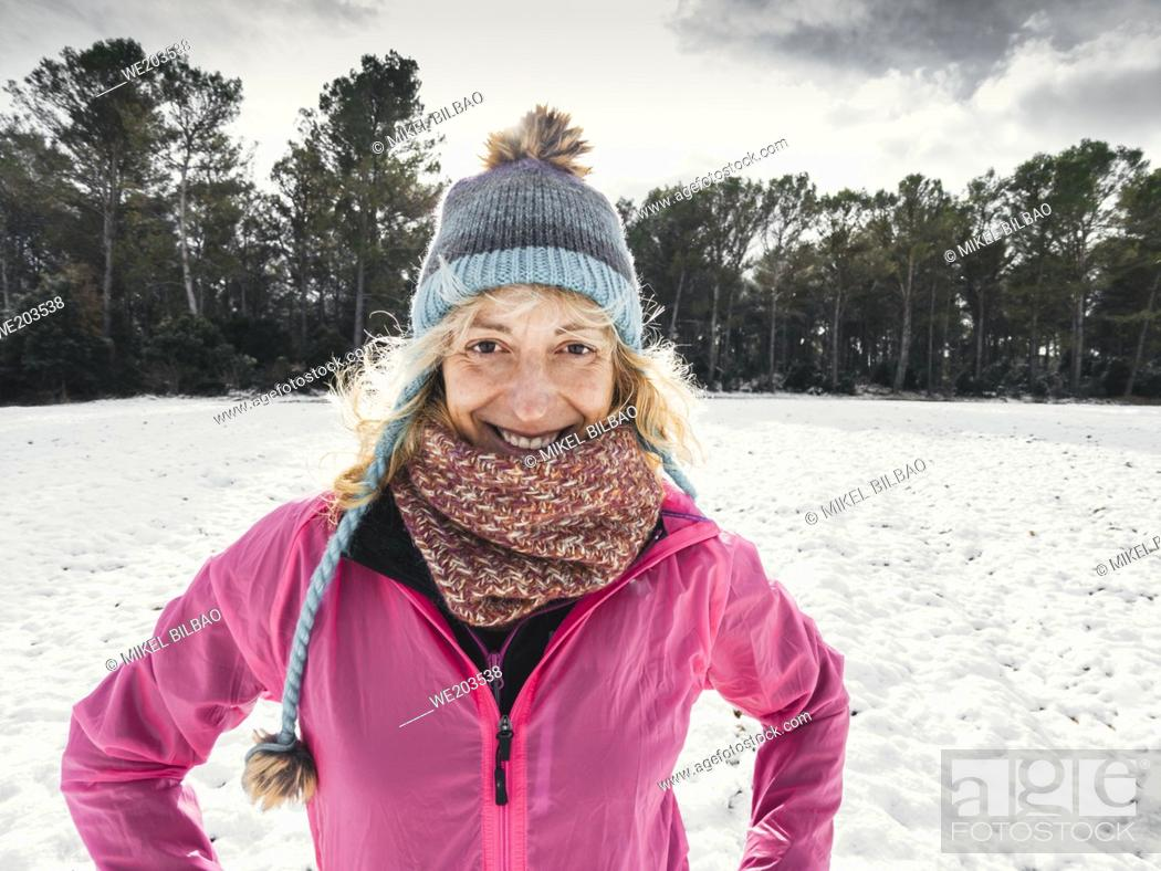 Stock Photo: Happy caucasian young woman with a hat and a pink raincoat enjoying snow outdoor in winter time. Navarre, Spain, Europe.