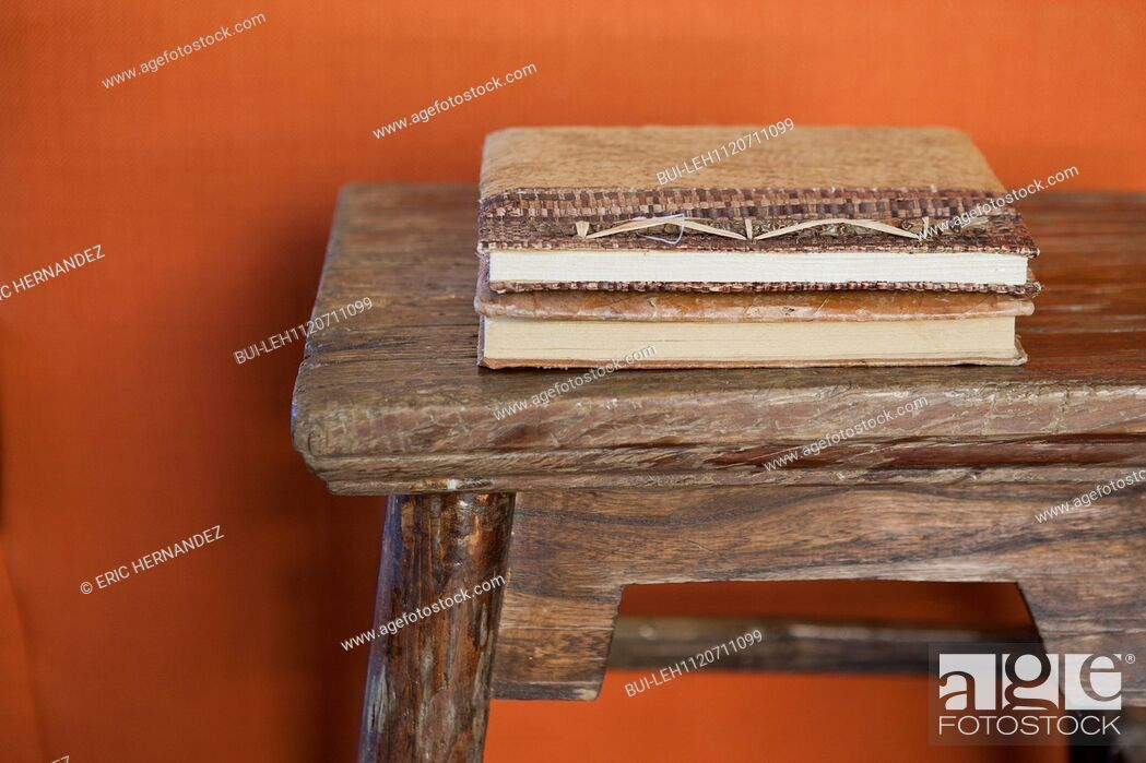 Imagen: Close-up of books on a cropped wooden table against orange wall; Azusa; California; USA.