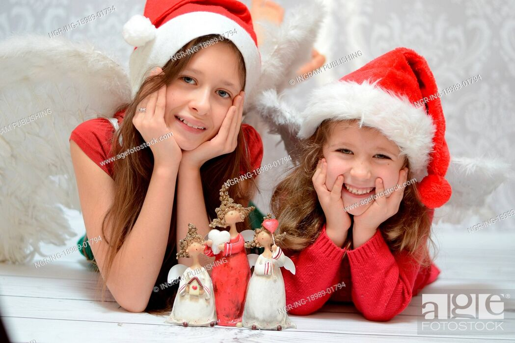 Stock Photo: Two delighted sisters with toy angels.