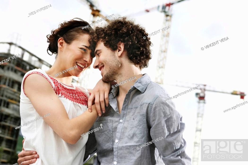 Stock Photo: Germany, Berlin, Young couple in front of new building, cranes in background.