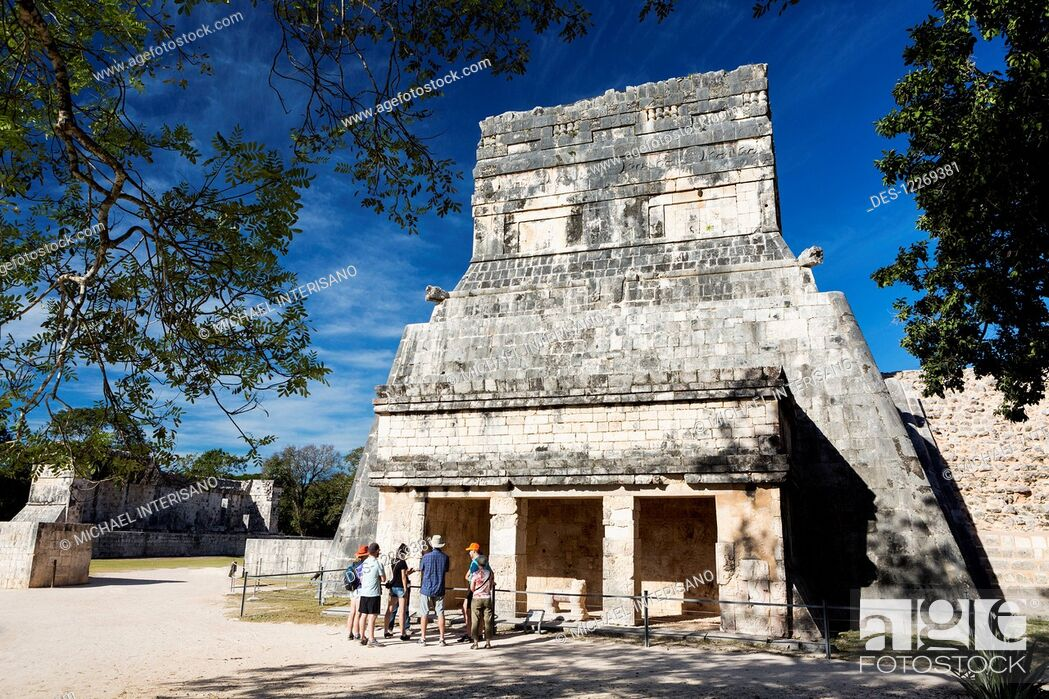 Stock Photo: Ancient Mayan Temple framed by trees with tourist on tour and blue sky; Chichen Itza, Yucatan, Mexico.