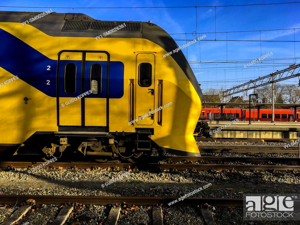 Imagen: Dordrecht, Netherlands. Yellow, Blue & Black double deck intercity train parked near the Railway Station, waiting for it's next ride to it's new destination.