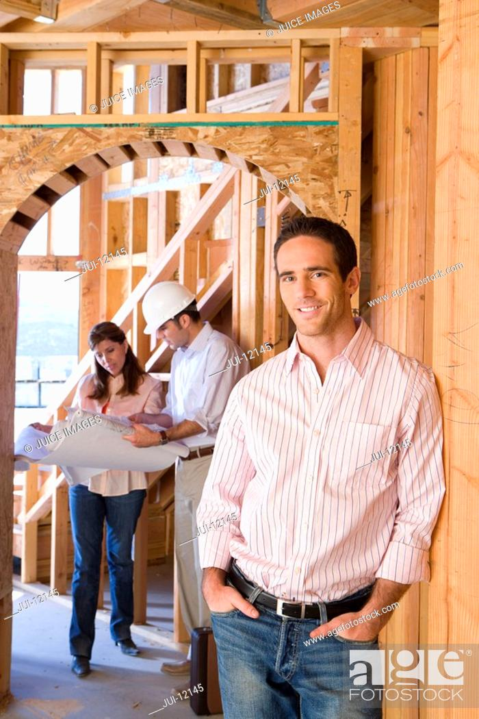 Stock Photo: Portrait of man smiling by architect showing blueprint to woman in partially built house.