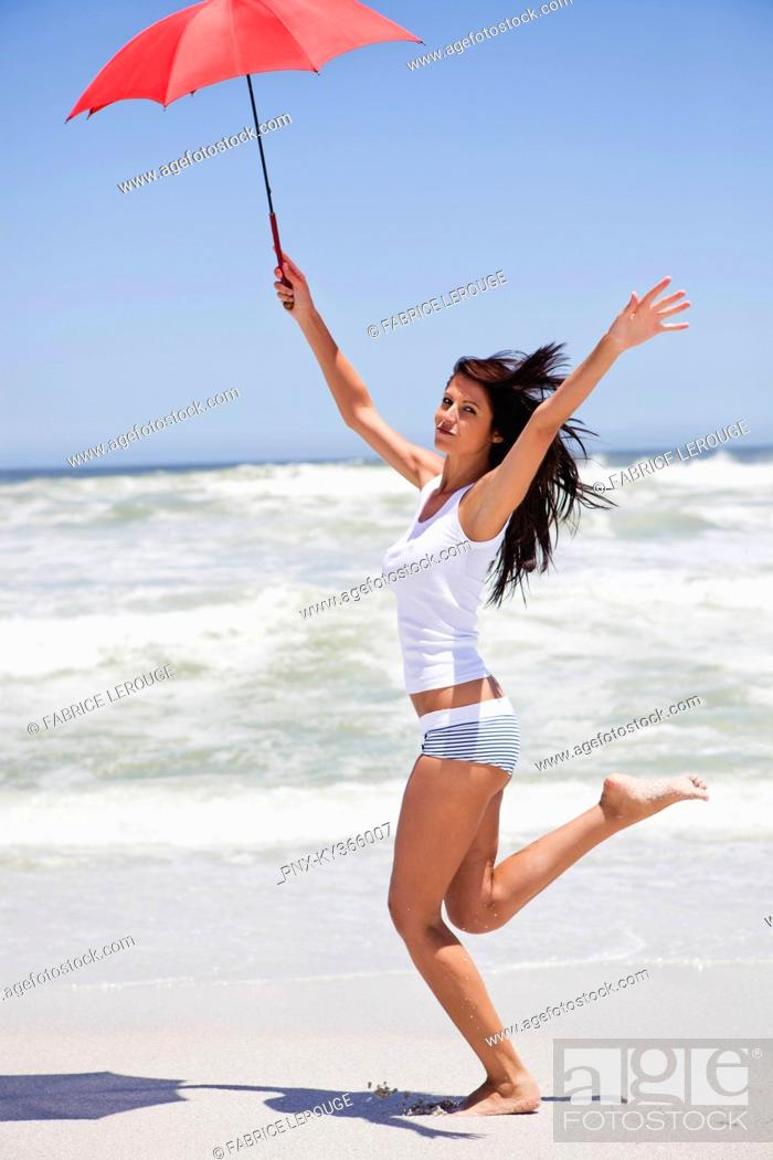 Stock Photo: Woman running on the beach with an umbrella.