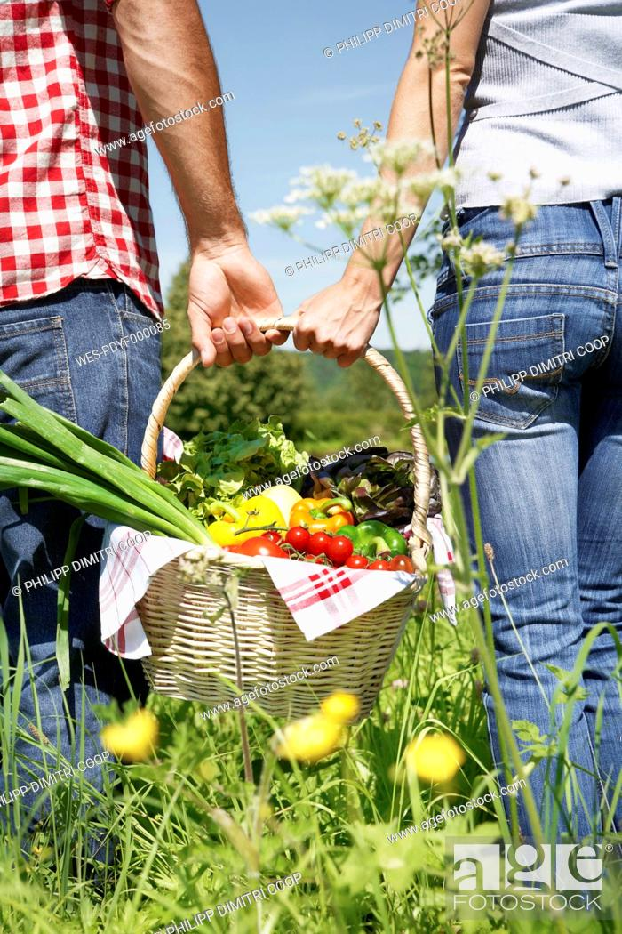 Stock Photo: Germany, Cologne, Young couple with picnic basket in meadow.