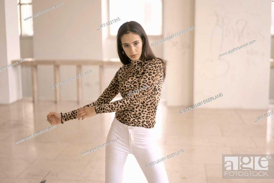 Imagen: confident woman dancing indoors, fashionable clothing style, movement, in Munich, Germany.