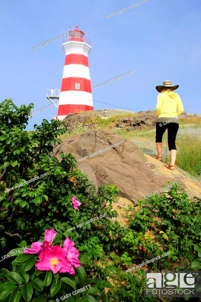Stock Photo: A woman walking up a slope to view the Brier island lighthouse in Nova Scotia, Canada.