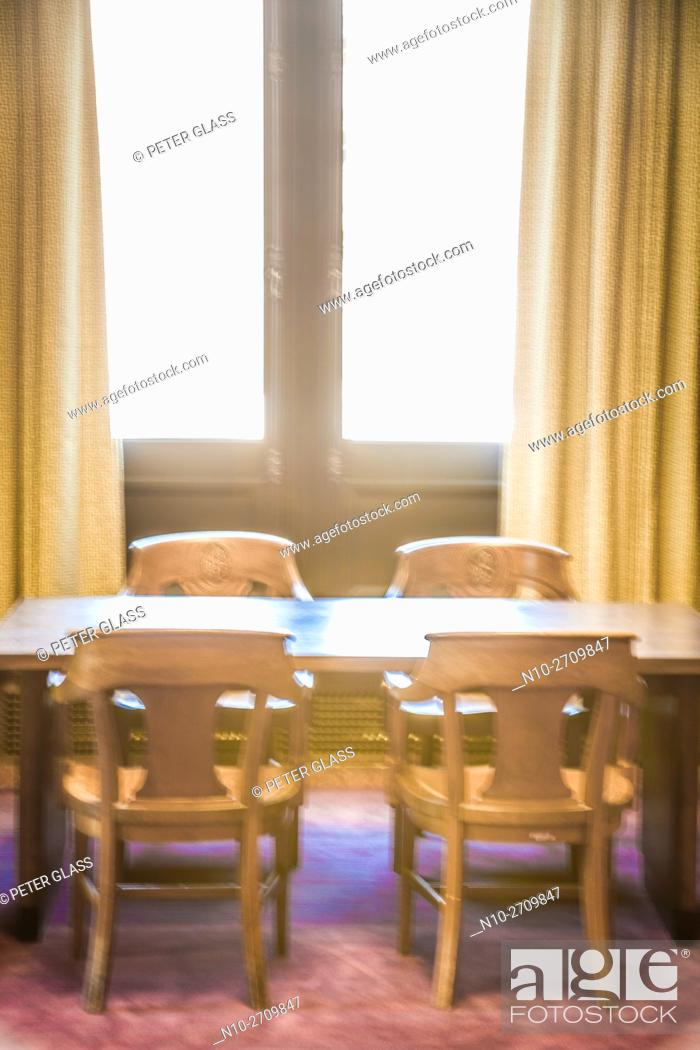 Stock Photo: Table and chairs near windows in a library.