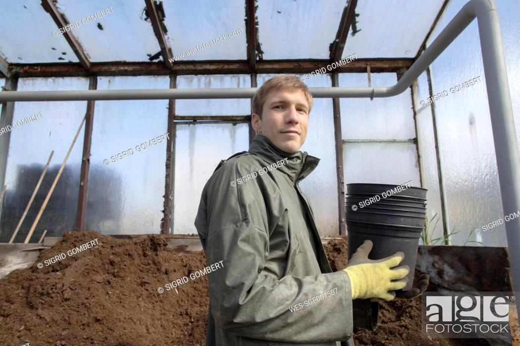 Stock Photo: Young gardener at work, filling mother soil.