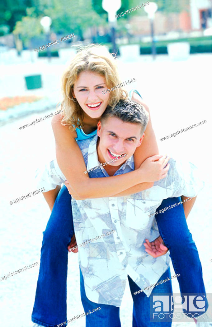 Stock Photo: Portrait of a young woman riding piggyback on a young man.