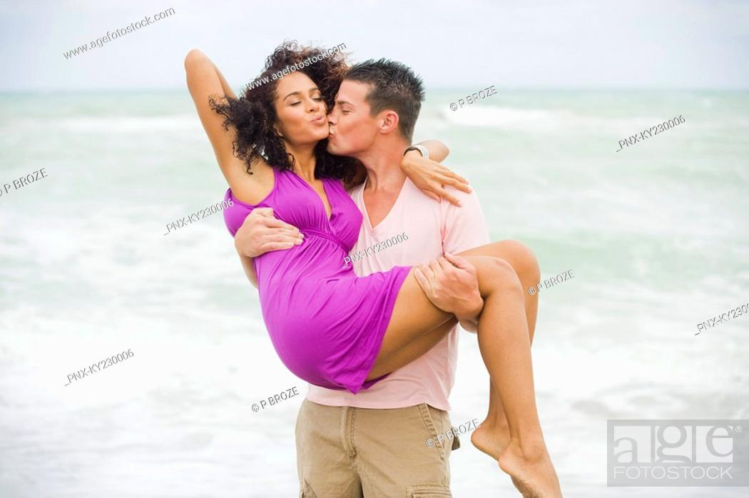 Stock Photo: Man carrying and kissing a woman on the beach.