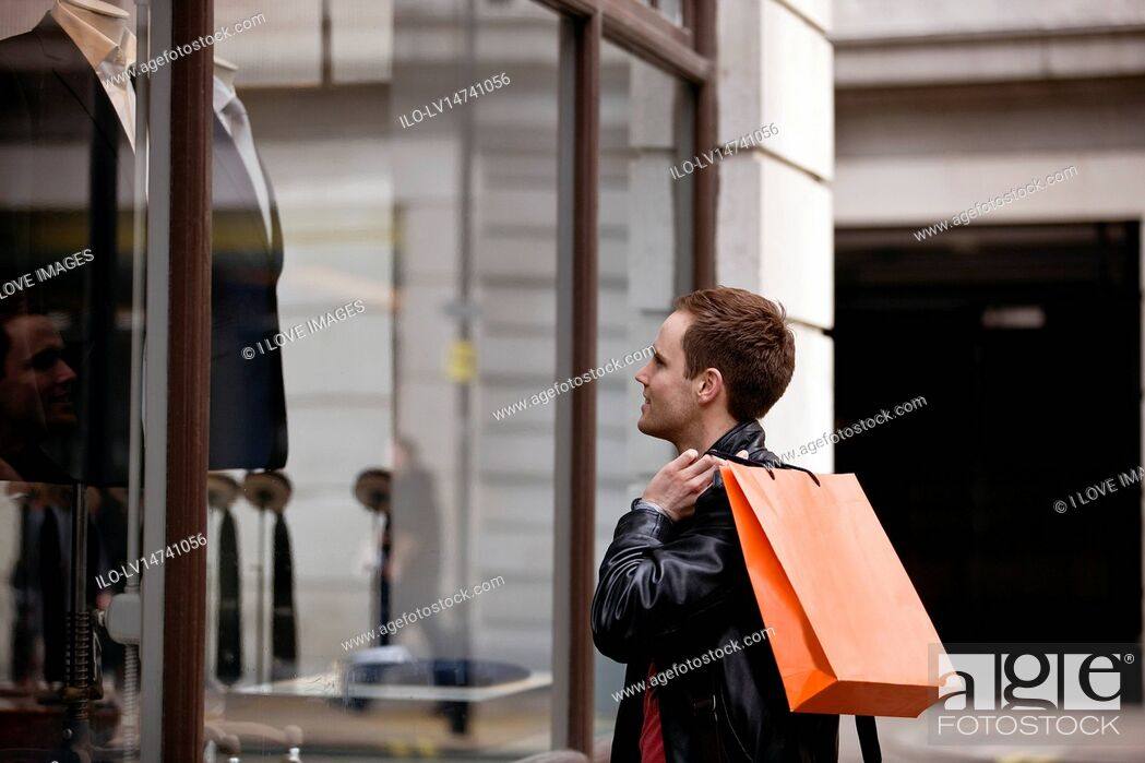 Stock Photo: A young man looking in a shop window.