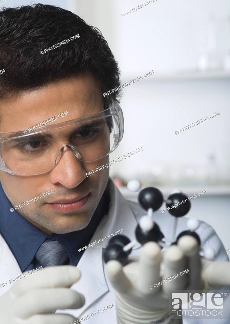 Stock Photo: Scientist holding molecular model in a laboratory.