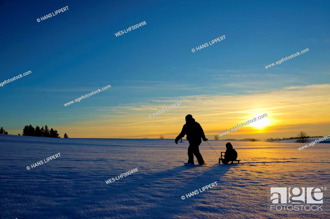 Stock Photo: Mother and daughter sledging at sunset.