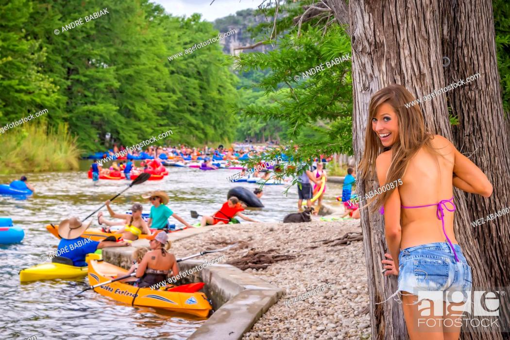 Stock Photo: USA, Texas, Young woman in bikini standing behind tree watching people tubing and kayaking the Frio River.