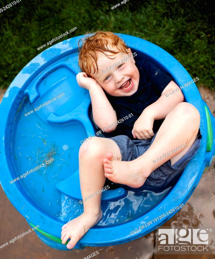Stock Photo: Toddler boy laying in water table with clothes on laughing in backyard.