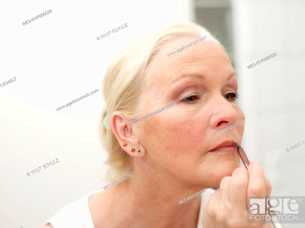 Stock Photo: Senior woman appyling lipstick, close up.