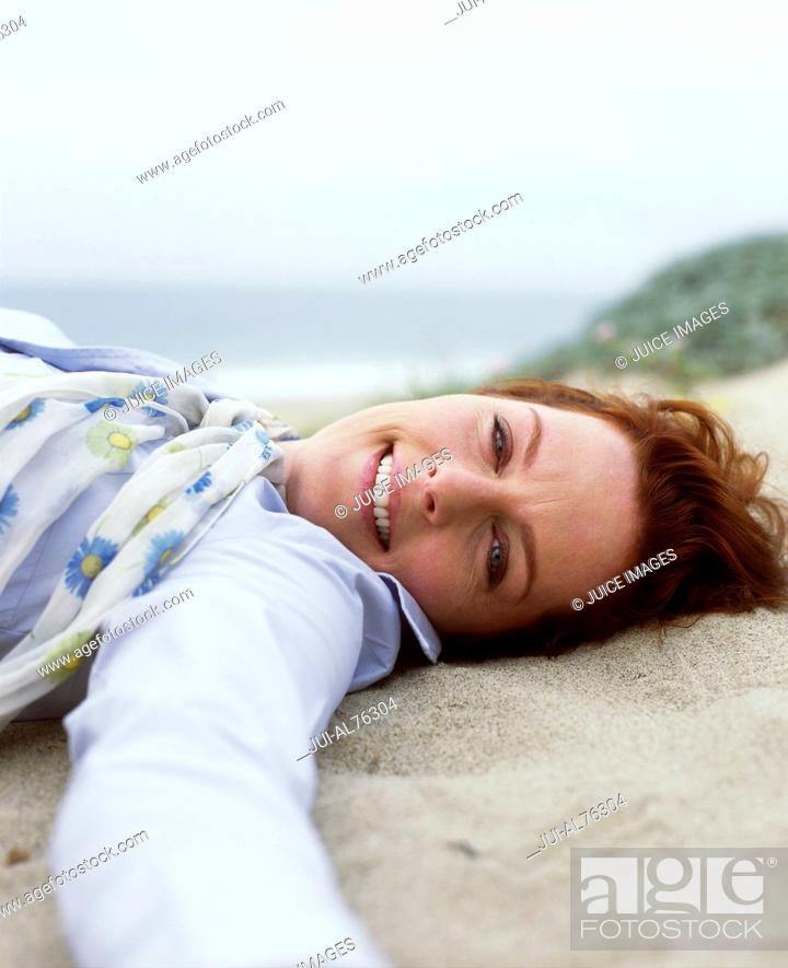 Stock Photo: Portrait of a middle aged woman lying on the sand on a beach.
