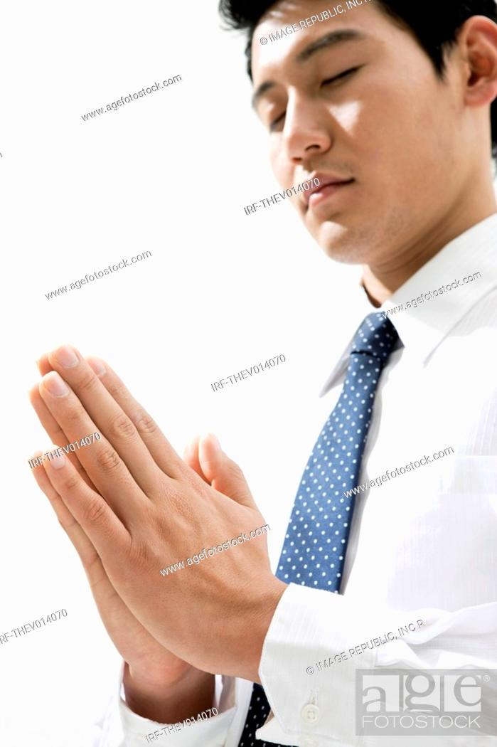 Stock Photo: businessman pray in putting his hands together.