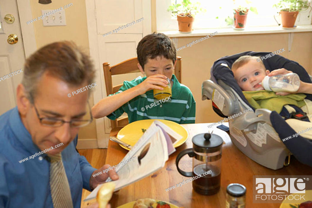 Stock Photo: High angle view of a mid adult man with his two sons sitting at a dining table.
