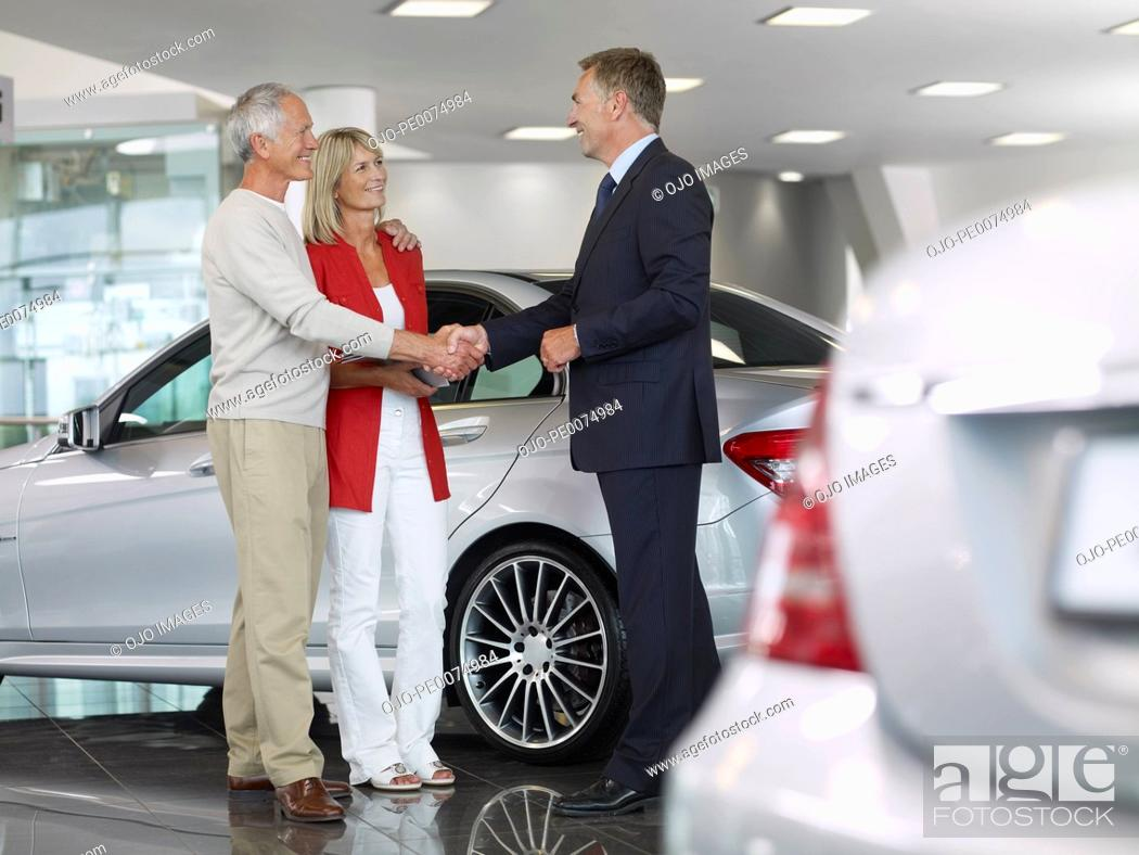 Stock Photo: Salesman shaking hands with couple in automobile showroom.