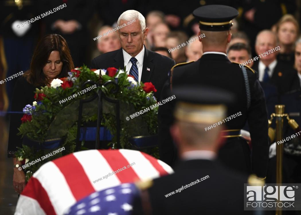 Stock Photo: US Vice President Mike Pence (C) and Second Lady of the United States Karen Pence (L) pay their respects at the casket bearing the remains of former US.