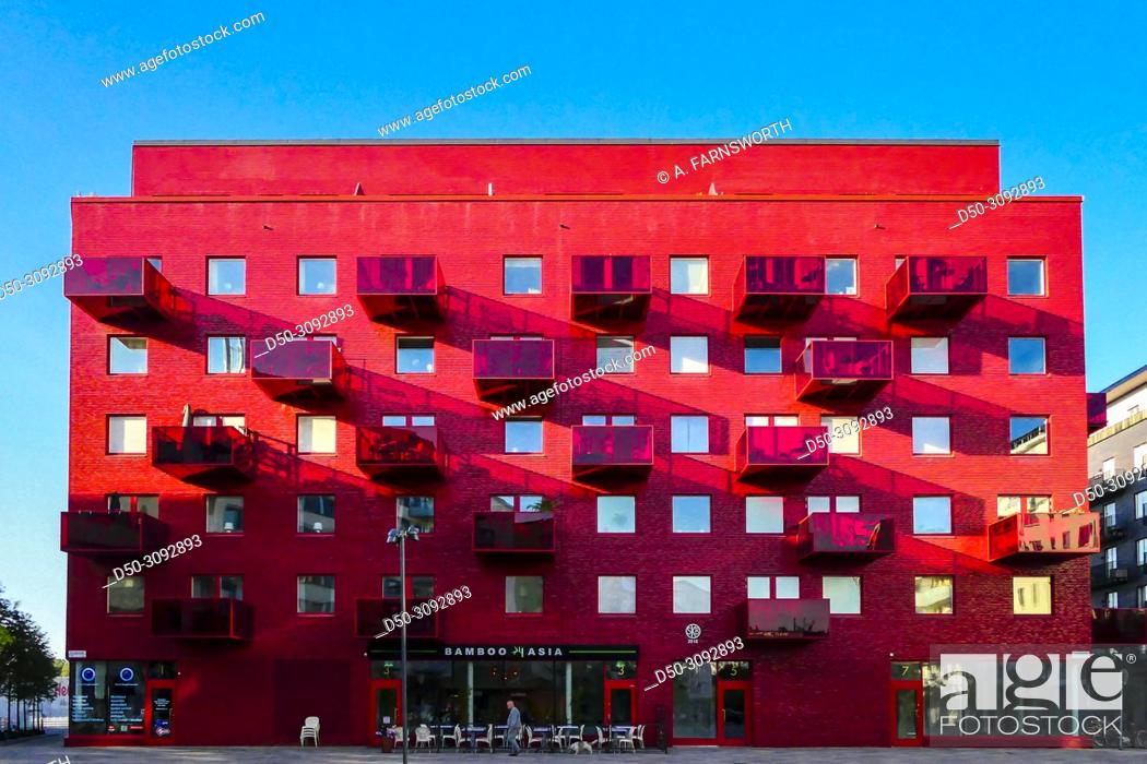Stock Photo: A red coop apartment building in area known as Norra Djurgarden on the Storangstorget. Also known as the Royal Seaport. Stockholm, Sweden.