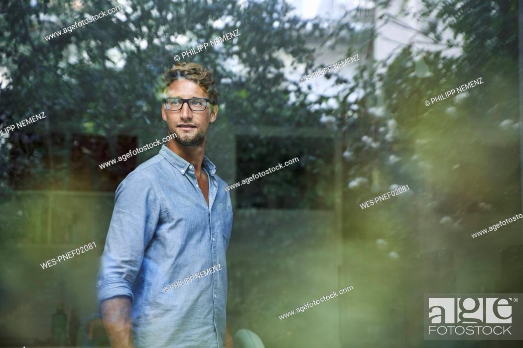 Stock Photo: Casual young businessman behind windowpane in office.