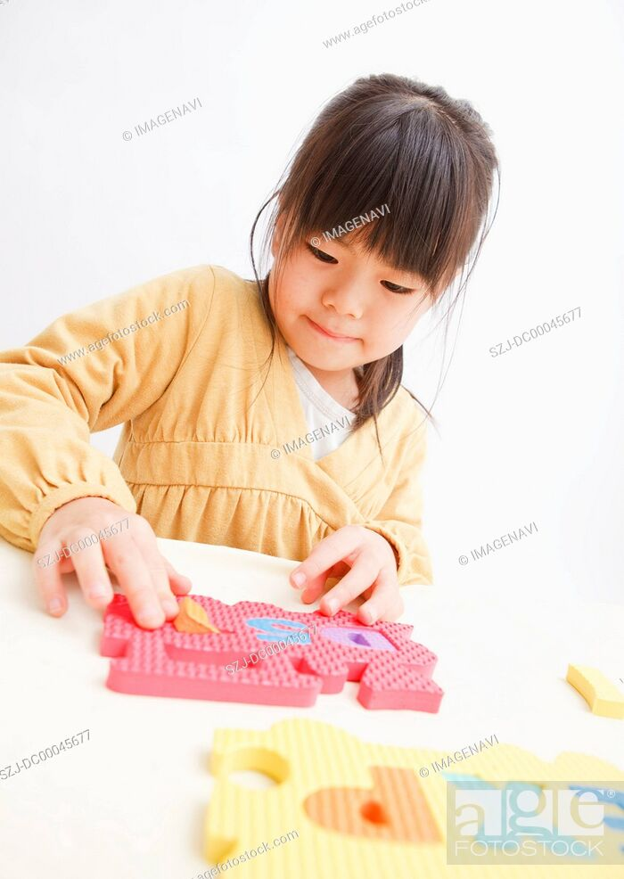 Stock Photo: Girl playing puzzle.