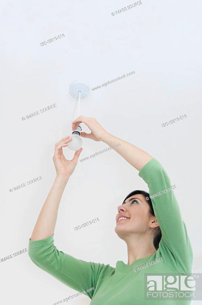 Stock Photo: Woman changing a lightbulb.