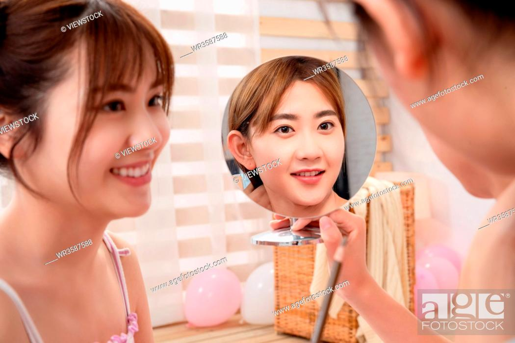 Stock Photo: Eyebrows girlfriends to the mirror in the bedroom.